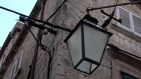 4K Bourdonnement hors du réverbère ou de la lampe accrochant sur la façade d'un bâtiment dans Dubrovnik clips vidéos