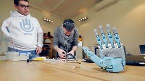 4K Braço protético biônico Coordenadores que desenvolvem o dispositivo robótico moderno - braço biônico video estoque