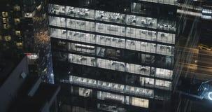 4K buitenkant die schot van een modern bureaugebouw vestigen bij nacht stock footage