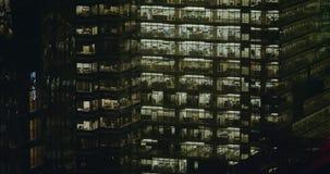 4K buitenkant die schot van een modern bureaugebouw vestigen bij nacht stock video