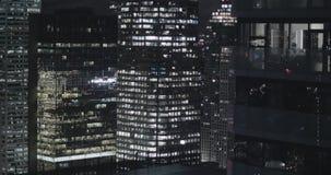 4K buitenkant die schot van een modern bureaugebouw vestigen bij nacht stock videobeelden