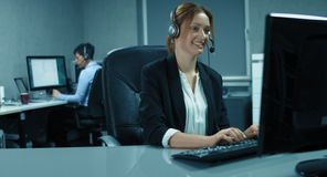 4K: A callcenter team is working in their office. The woman in the front is using a headset stock video