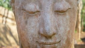 4K. Calm and peaceful face of old worship buddha statue head illuminated. Buddha statue at Chiangmai history temple. Chiang Mai