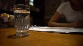 4K camarero Serving un vidrio de agua con el limón en el restaurante con la tabla de madera almacen de video