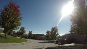 4k Car interior driving down road looking out front windshield on a sunny day. A car ride down road in residential suburban neighborhood looking at trees, houses stock footage