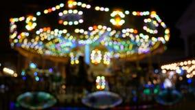 4K carosello astratto di girotondo del ` s dei bambini della sfuocatura alla notte con la luce del bokeh sul festival per fondo video d archivio