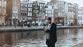 4K Casual Caucasian man in hat using smartphone. Handsome bearded creative businessman texting on a river embankment. 4K Casual Caucasian man in hat using stock video