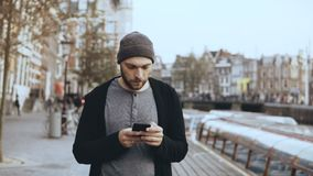 4K Casual concentrated man using smartphone. Handsome bearded creative European male in hat texting in the street. 4K Casual concentrated man standing outside stock video footage