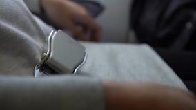 4k, ceinture de sécurité asiatique d'attache de femme sur l'avion Passagers utilisant la ceinture de sécurité banque de vidéos