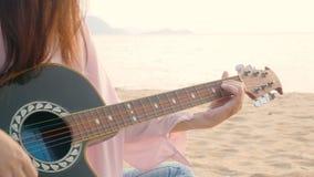 4K cercano para arriba de mujer larga del pelo tocar la guitarra acústica en la playa con el viento apacible durante el tiempo de metrajes