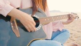 4K cercano para arriba de mujer larga del pelo tocar la guitarra acústica en la playa con el viento apacible durante el tiempo de almacen de metraje de vídeo