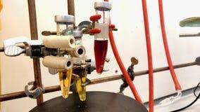 4K chemische reactie van donkere bruine oplossing binnen kleine microgolfflesjes op een magnetische rotor stock videobeelden