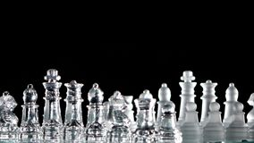 4K. Chess pieces is standing on glass board. Chess pieces is standing on glass board. Black background. Rotation cam stock footage