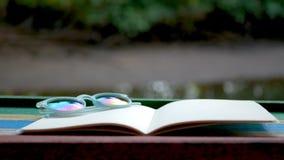 4K Cinemagraph del libro in bianco con il vaso da fiori sulla tavola di legno contro i precedenti scintillanti del fiume archivi video