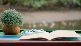 4K cinemagraph do livro vazio com o vaso de flores na tabela de madeira contra o fundo efervescente do rio filme