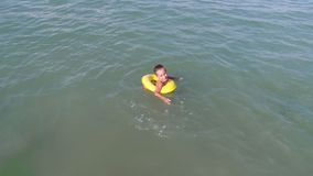 A young simpotic boy is floating in blue sea water. stock video