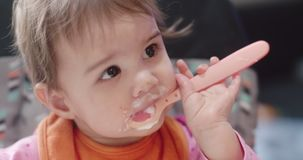4K Cinematic portrait of a 10 month old baby girl being spoon fed yogurt.