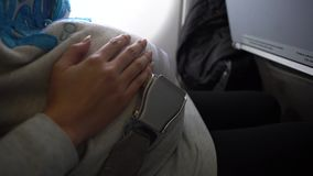 4k, cinturón de seguridad asiático de la cerradura de la mujer embarazada dentro del aeroplano Recorrido seguro almacen de video