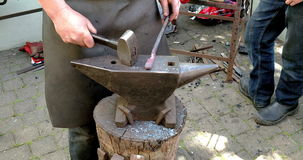 A 4K close up of a blacksmith hammering and forging steel on an anvil, shot in Ireland stock video footage