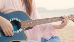 4K. close up of long hair woman playing acoustic guitar at the beach with gentle wind during sunset time, feeling relax.  stock video