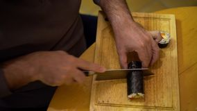 4K, Close-up of man chef hands cutting with knife a japanese Makizushi food stock footage