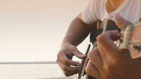 4K. close up of a man playing acoustic guitar at the beach during sunset time, feeling relax.  stock video