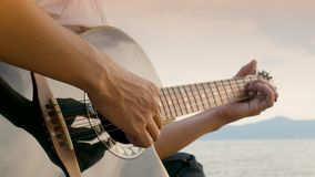 4K. close up of a man playing acoustic guitar at the beach during sunset time, feeling relax.  stock video footage