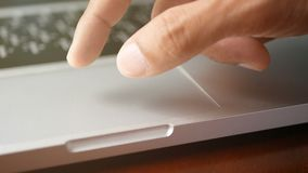 4K. close-up a man working with notebook laptop, using finger with keyboard and touchpad or trackpad for slide and zoom in, zoom. Out stock footage
