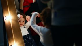 Close-up shot. Little girl looks in the mirror and daces with her arms up stock footage