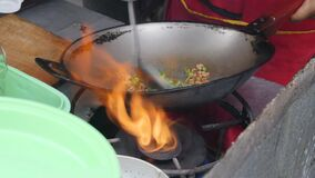 4K Close up of Thai street food vendor cooking a hot chilli chicken pork stir fry in large wok. these vendors are found