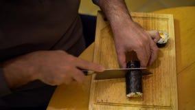4K, Close-up van de handen die van de mensenchef-kok met mes een Japans Makizushi-voedsel snijden stock footage
