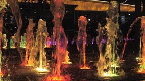 Close-up view of beautiful colorful fountain on city street at night. stock footage