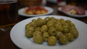 4K, Close up woman hands holding a green olive in spanish bar. Typical tapa stock video