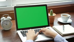 4K. close-up woman working with notebook laptop, using finger with keyboard for typing. computer laptop with blank green screen stock footage