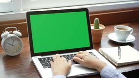 4K. close-up woman working with notebook laptop, using finger with keyboard for typing. computer laptop with blank green screen stock video footage