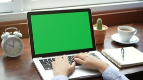 4K. Close-up woman working with notebook laptop, using finger with keyboard for typing. computer laptop with blank green screen. Chroma key stock footage