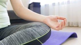 4k closeup dolly video of young woman sitting in lotus asana and meditating. Girl practicing yoga at home