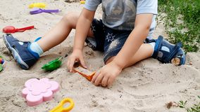 4k closeup video of adorable toddler boy digging sand with scoop in sandbox at park. 4k closeup footage of adorable toddler boy digging sand with scoop in stock video
