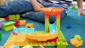 4k closeup video of colorful ball rolling in toy marble run built by little toddler boy