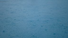 4K. closeup footage rain drop on clear blue water surface with sky and clouds reflect on water surface. rain drizzle rainfall stock video