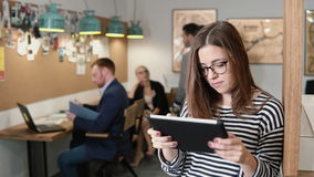 4k. closeup young attractive brunette businesswoman uses a touchscreen tablet in the modern startup office. 4k. closeup attractive brunette businesswoman uses a Royalty Free Stock Photos