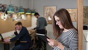 4k. closeup young attractive brunette businesswoman uses a touchscreen tablet in the modern startup office. 4k. closeup attractive brunette businesswoman uses a Royalty Free Stock Photo