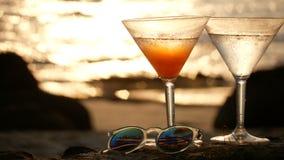4K Cocktailglas met waterdruppeltjes op het strand met gouden golfbezinning met hart bokeh tijdens de zonsondergangtijd stock videobeelden