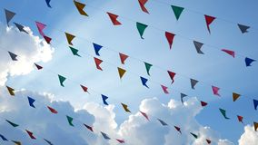 4K. colorful design decoration triangular fair flags blowing on the wind hanging on blue sky background for fun festival party. Event, feast celebration holiday stock video footage