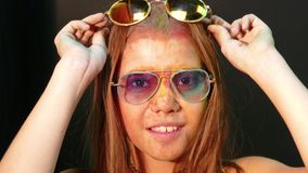 4k Colourful. Woman in Holy Powder Smiling at camera. 4k video. On the girl`s face the traces of paint, shot on a black background. The teenager wore sunglasses stock video footage