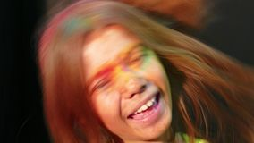 4k Colourful. Woman in Holy Powder Smiling at camera. 4k video. On the girl`s face the traces of paint, shot on a black background. The teenager wore sunglasses stock footage