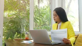 4K. confident Asian business woman reading agreement, typing on a laptop keyboard and working with document paper work stock footage