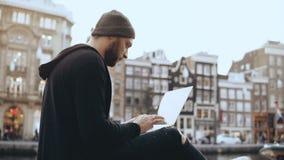 4K creatieve mensenzitting met laptop in de straat Werkend mobiel bureau De Oude Stad van Amsterdam Atmosferische cityscape stock videobeelden