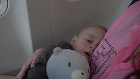 4k - cute little baby sleeps on the hands of his mother during airplane flight. stock video footage