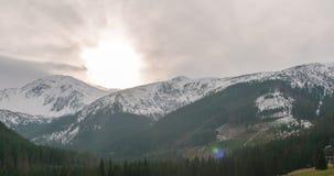 4K czasu upływ góry grań z śniegiem, słońcem i chmurami jadącymi silnym wiatrem, zbiory